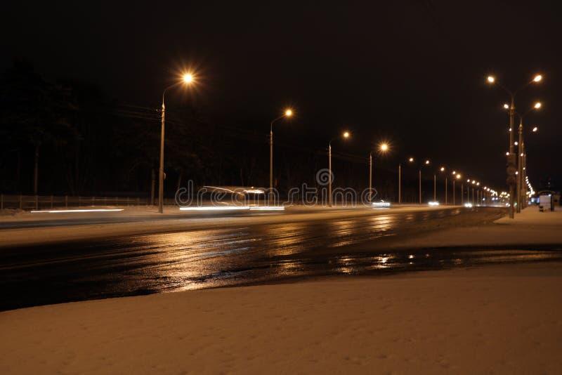 Bilar på vintervägen med snö Farlig biltrafik i dåligt väder med bokeh på natten som använder bakgrund fotografering för bildbyråer