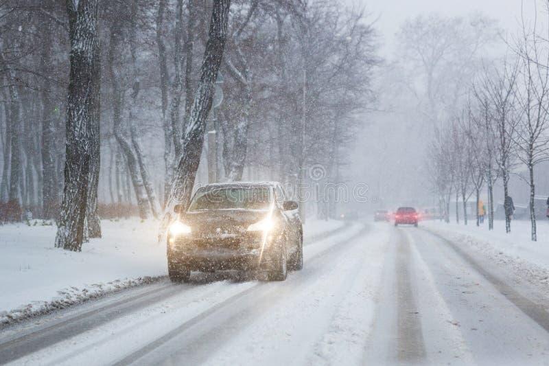 Bilar som flyttar sig på den hala snöig vägen på stadsgatan under tungt snöfall på aftonen i vinter Förfallen häftig snöstorm för fotografering för bildbyråer