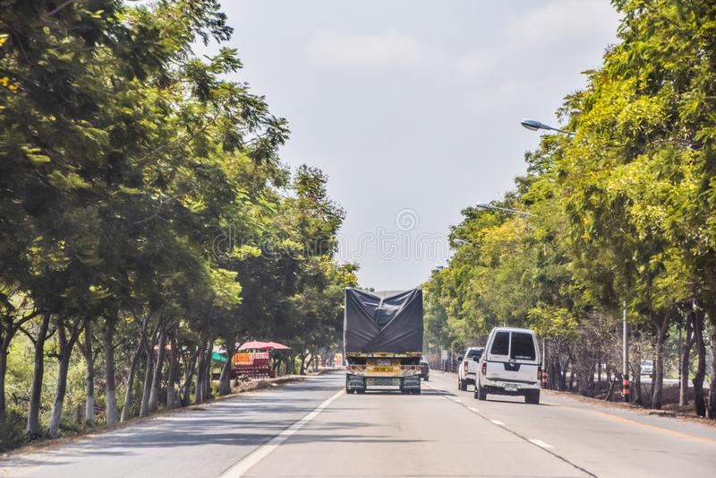 Bilar som kör passera lastbilar på lantliga vägar i mitt av träd och varmt väder på Thailand - April 16, 2019 royaltyfri fotografi