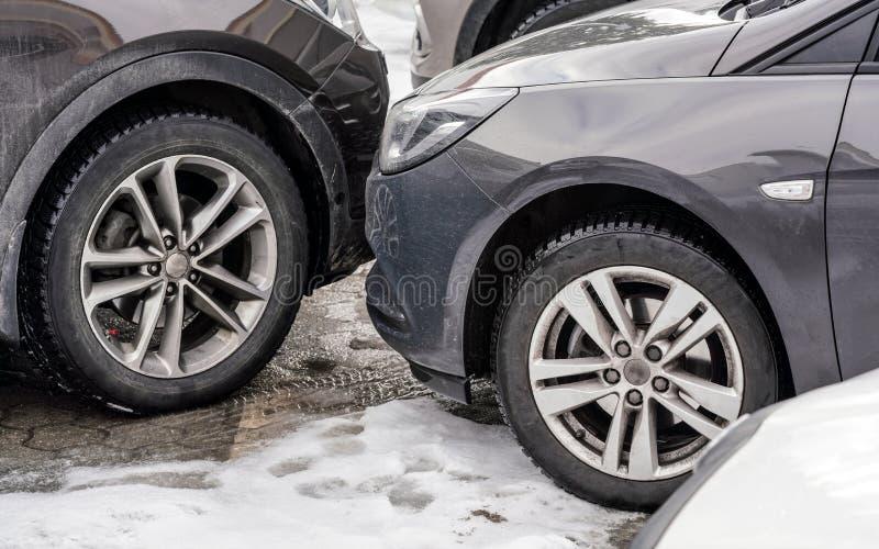 Bilar som nästan parkerades med stötdämpare, detaljen på smutsig framdel och gummihjul på snö, täckte jordning arkivfoton