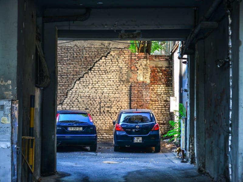 Bilar som parkerar på det gamla tegelstenhuset arkivfoto