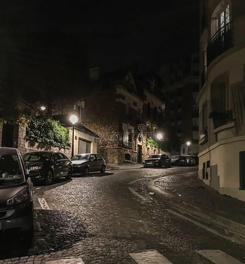 Bilar som parkeras på en tyst kullerstengata på natten på Montmartre, Paris, Frankrike arkivfoton