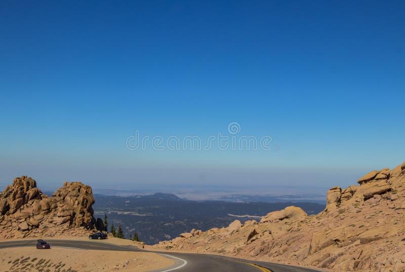 Bilar som parkeras på kanten av den krökta bergvägen ovanför trädlinjen på pikar maximala Colorado med folk som klättrar kala ste royaltyfria foton