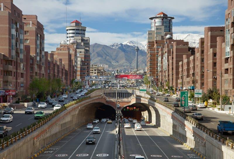 Bilar som passerar till och med den Navvab tunnelen av Teheran med Milad Tower i bakgrunden royaltyfri foto