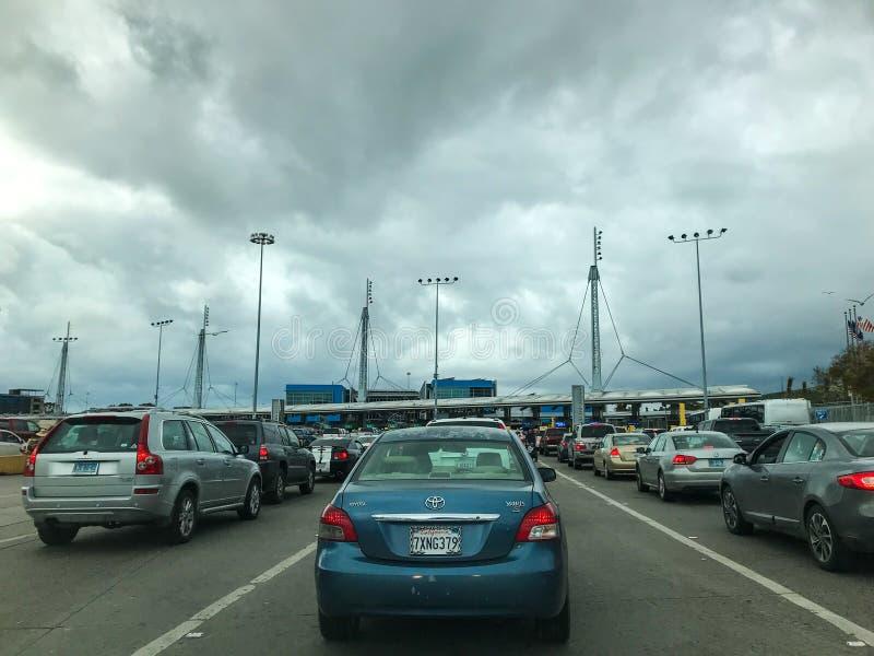 Bilar som väntar i linje för att korsa gränsen från Mexico till USA royaltyfri bild