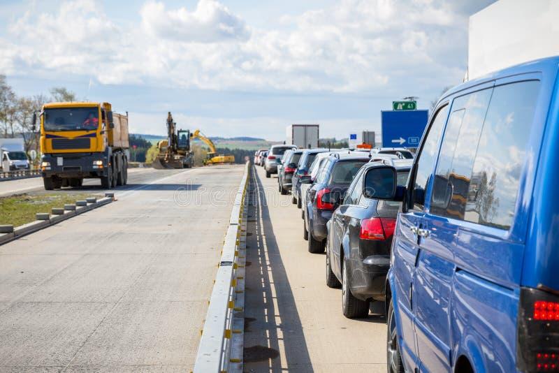Bilar ställer upp på vägkonstruktionen för motorvägen tack vare royaltyfri foto