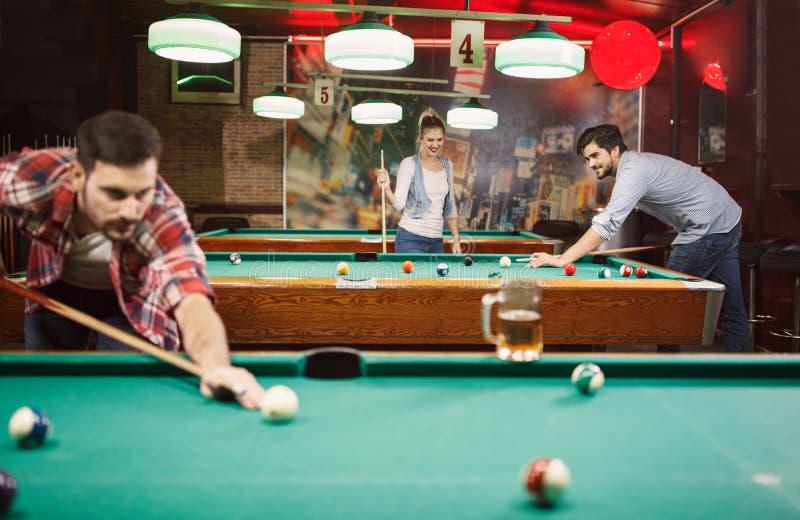 Bilardowe gry - szczęśliwi przyjaciele cieszy się bawić się basenu wpólnie zdjęcie royalty free