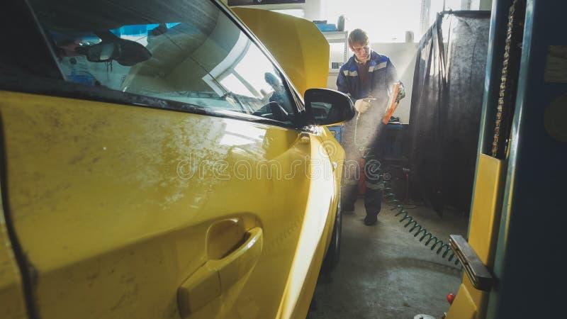 Bilautomatiskservice - mekanikern skruva av detaljen av bilen i huv arkivfoton