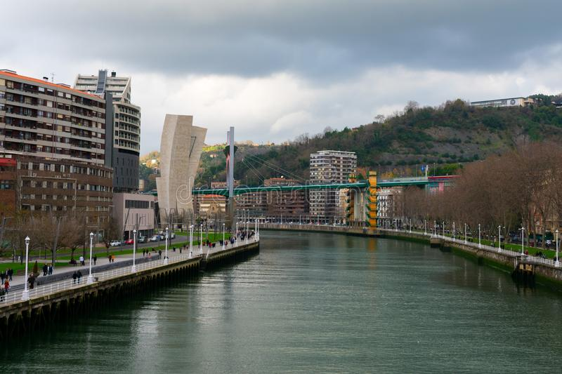 Bilbao, Spain/Europe; 29/12/18: Red modern bridge of La Salve crossing Nervion river in the city of Bilbao, Spain. Suspension, zubia, footbridge, building stock photo