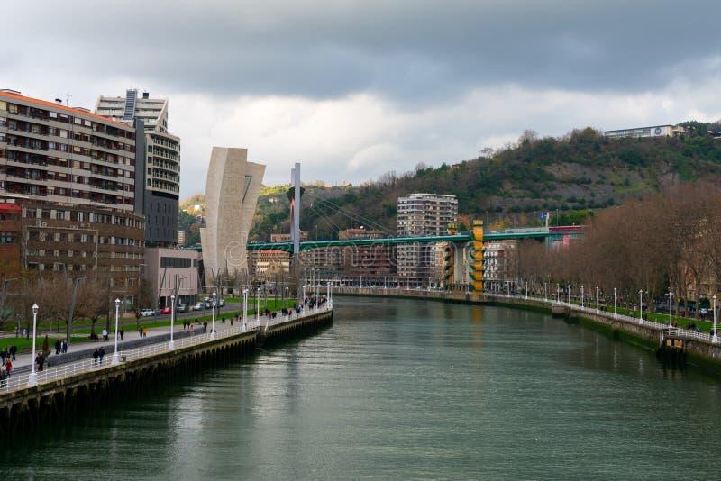 Bilbao, Spain/Europe; 29/12/18: Red modern bridge of La Salve crossing Nervion river in the city of Bilbao, Spain. Suspension, zubia, footbridge, building stock photo