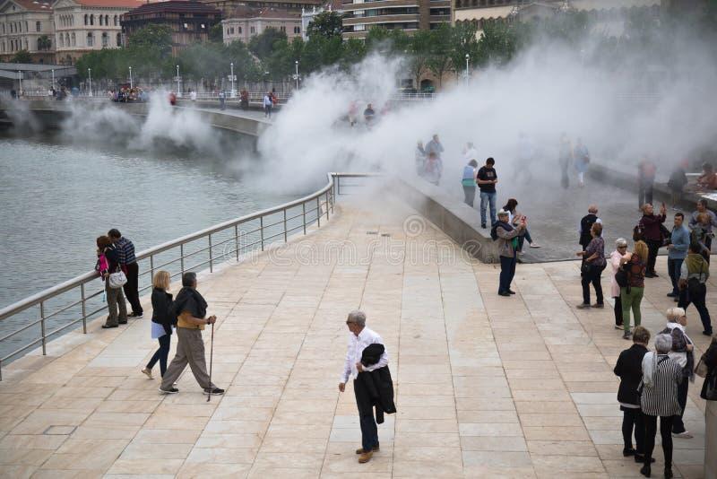 Bilbao, Spanje - Mei 17, 2017: mensen die en stad van Bilbao in de aantrekkelijkheidsanimatie van de waterrook lopen bezienswaard stock foto's