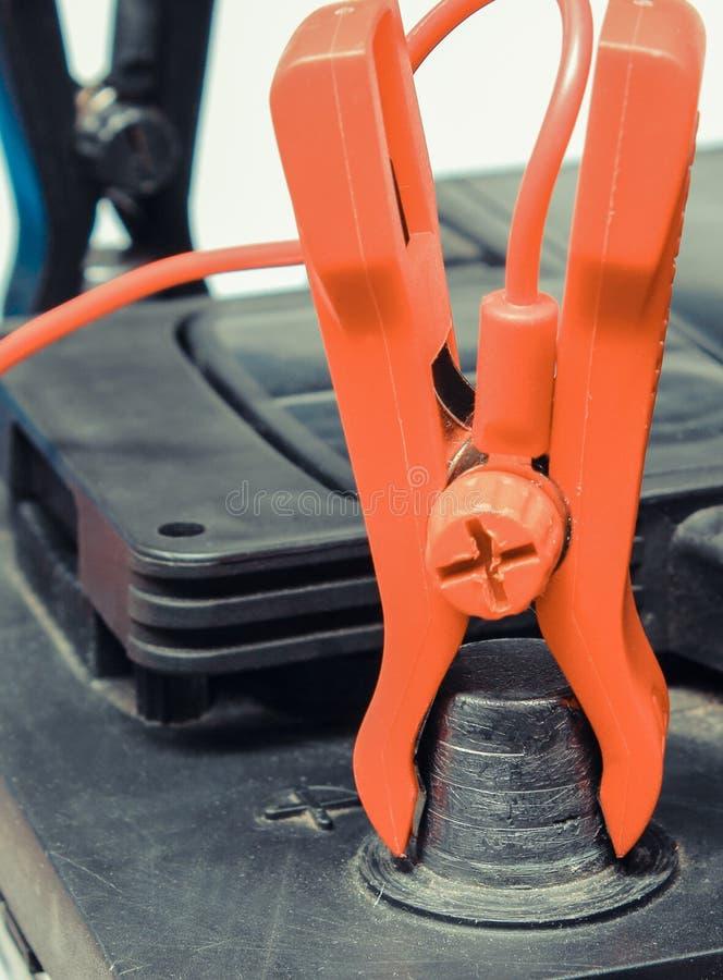 Bilbatteri med klämmor och anslutna kablar till laddare royaltyfria foton