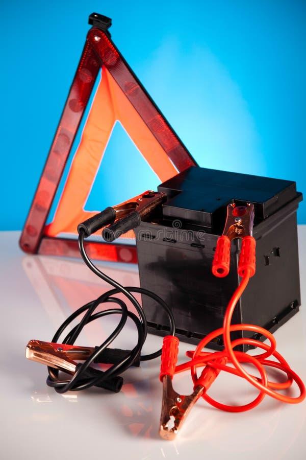Bilbatteri med två förklädekablar som fästas ihop på livligt motobegrepp royaltyfri bild