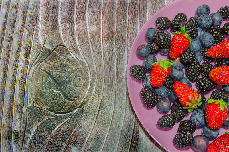 Bilberries And Strawberries On A Pink Plate Stock Photos