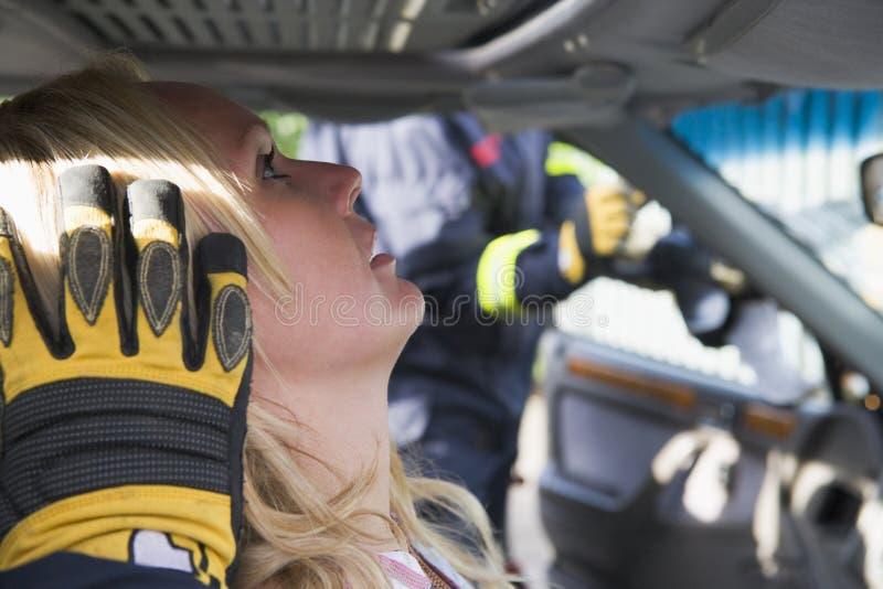 bilbrandmän som hjälper den sårada kvinnan royaltyfri bild