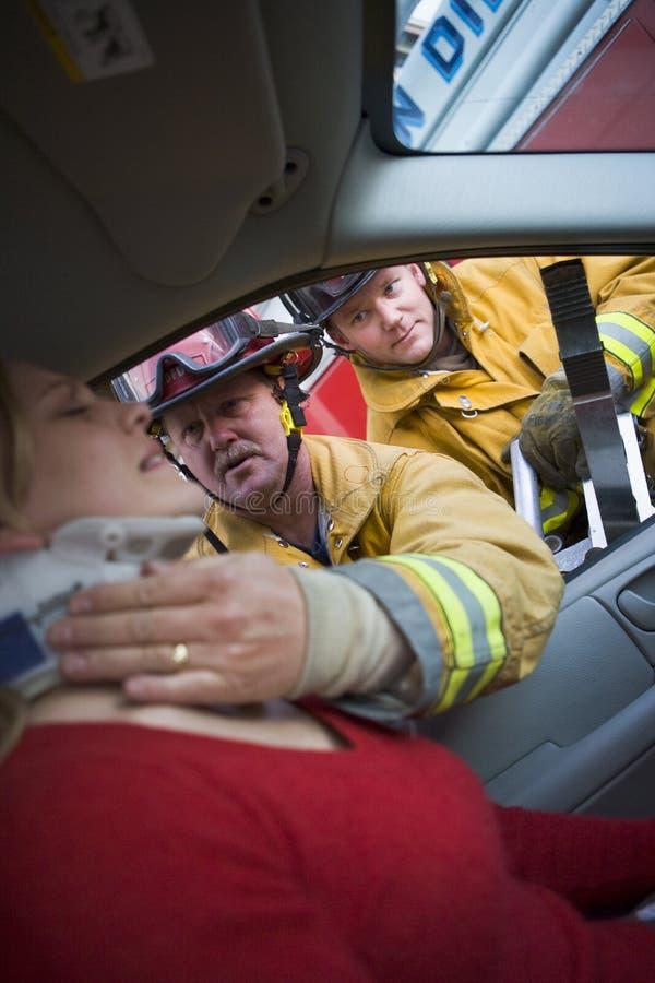 bilbrandmän som hjälper den sårada kvinnan royaltyfri fotografi