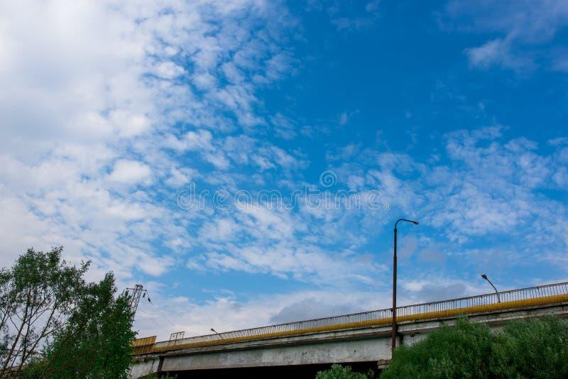 Bilbro mot den blåa himlen med moln arkivfoton