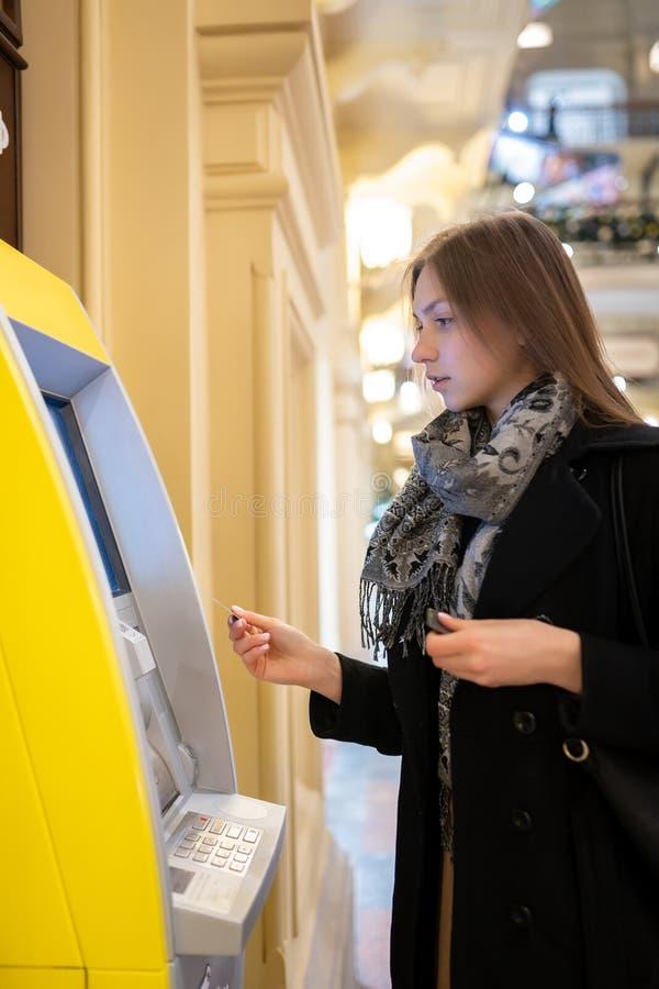 Bild auf Seite des jungen Brunette mit Bankkarte an ATM auf unscharfem Hintergrund stockfoto