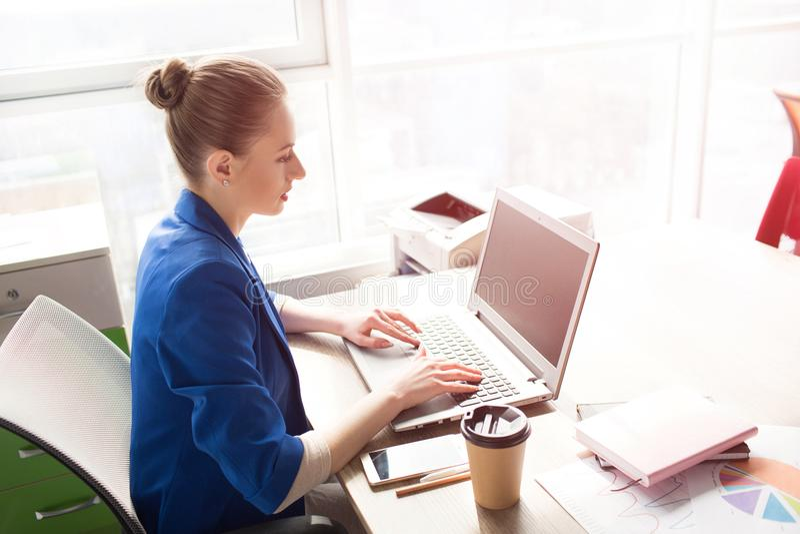 Bild av affärskvinnan i sammanträde för blått omslag på tabellen nära ljust fönster och arbete Hon skriver på keybord royaltyfri foto