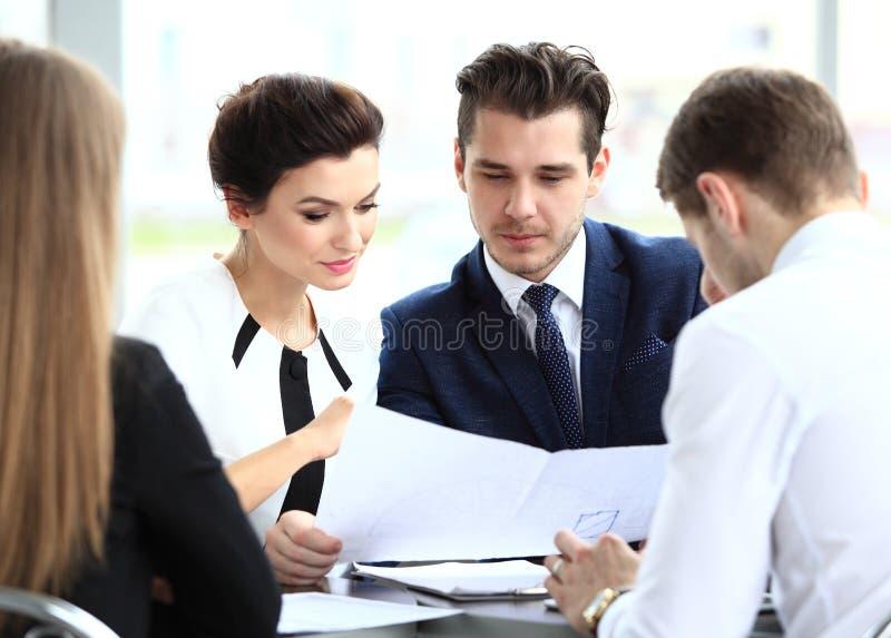 Bild av affärspartners som diskuterar dokument och idéer arkivbild