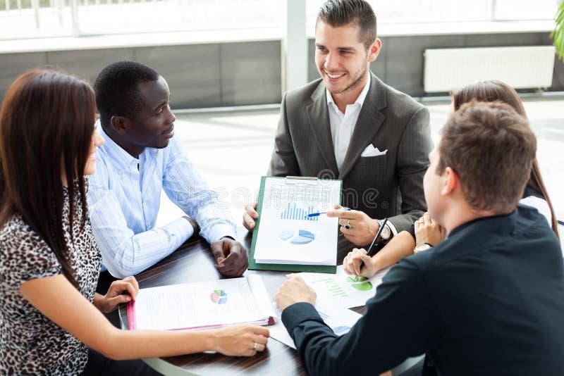 Bild av affärspartners som diskuterar dokument och idéer på mötet arkivfoto