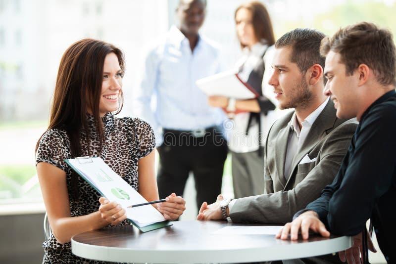 Bild av affärspartners som diskuterar dokument och idéer på mötet arkivbild