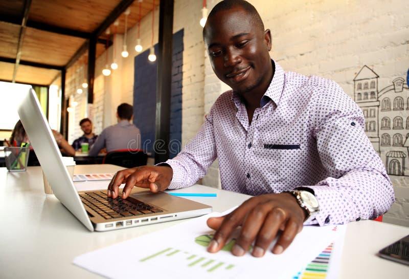 Bild av afrikansk amerikanaffärsmannen som arbetar på hans bärbar dator Stilig ung man på hans skrivbord arkivfoton