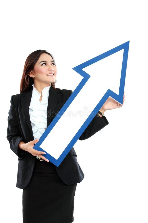 Bild av att le affärskvinnan med riktningspiltecknet fotografering för bildbyråer