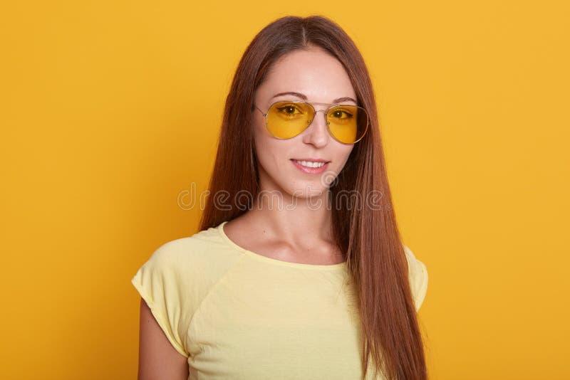 Bild av att le den mörka haired kvinnan med perfekt hud i glasögon som poserar och ser kameran över gul bakgrund, slump royaltyfri fotografi