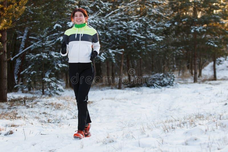 Bild av att le idrottskvinnan i gymnastikskor på morgonkörning mot bakgrund av träd i vinter arkivfoton