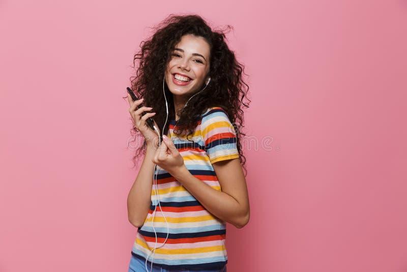Bild av att le kvinna20-tal med den innehavsmartphonen för lockigt hår royaltyfri foto