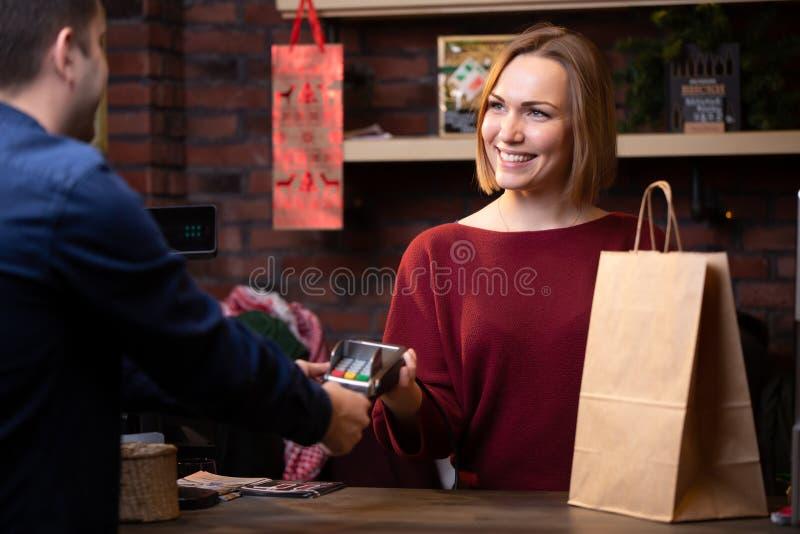 Bild av att le säljarekvinnaanseende bak manlig köparen för den kassaapparat och från tillbaka royaltyfria foton