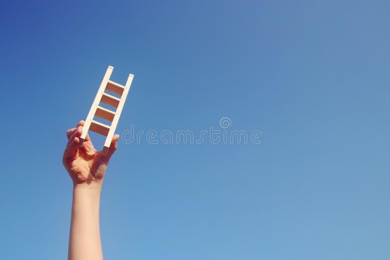 Bild av barnhanden som rymmer en stege mot himlen Utbildning och framgångbegrepp royaltyfri fotografi