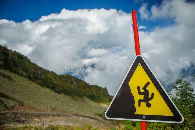 Bild av berglutningen, molnig himmel och varningstecknet royaltyfri foto