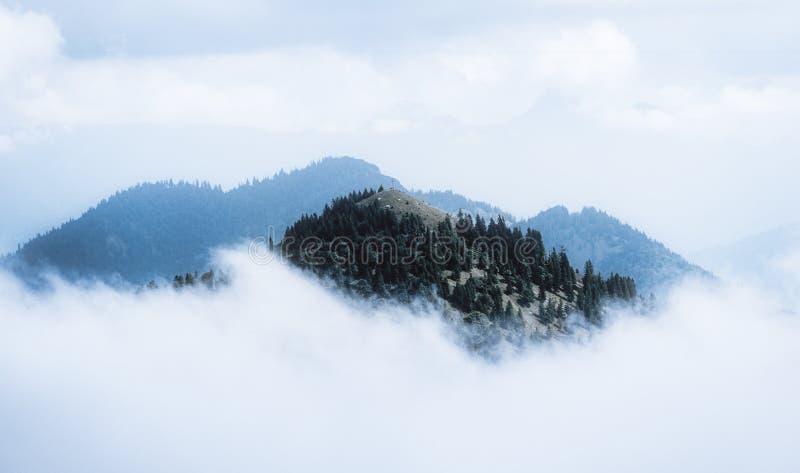Bild av bergmaximumet med korset som omges av moln arkivbilder