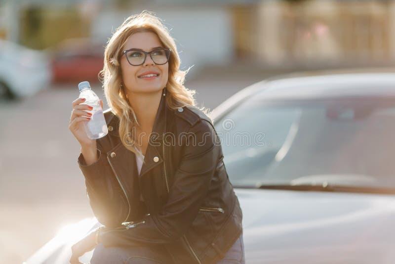 Bild av blondinen i exponeringsglas med flaskan av vatten i händer som sitter på huven av bilen royaltyfria bilder