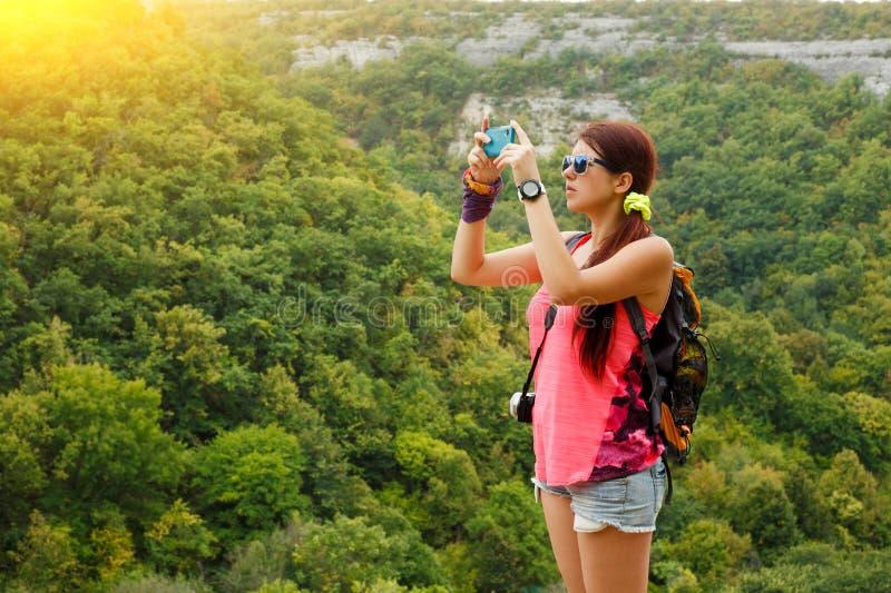 Bild av brunetten som fotograferar berget med vegetation royaltyfri foto