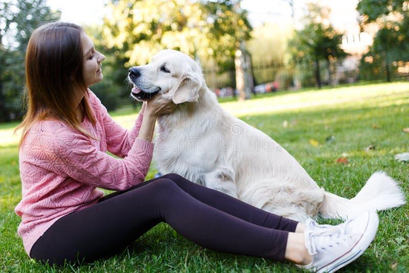 Bild av brunetten som kramar labrador på gräsmatta royaltyfria foton