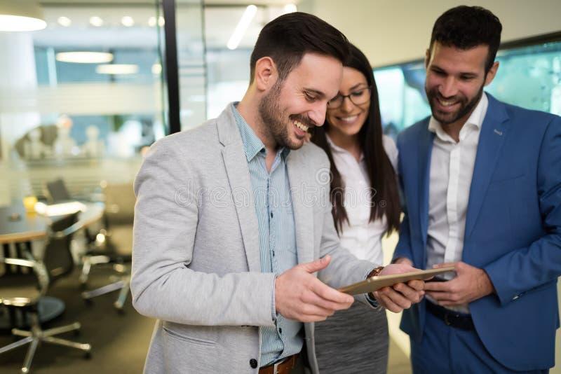 Bild av businesspeople som i regeringsställning använder den digitala minnestavlan arkivbilder