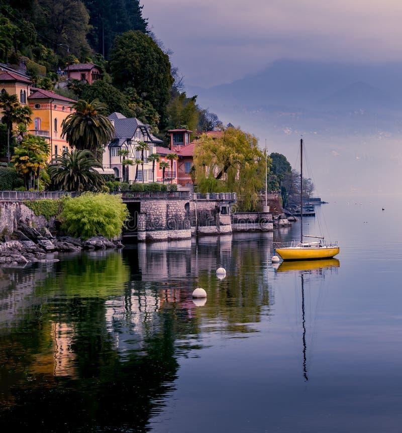 Bild av canneroen riviera p? sj?maggioren med den gula segelb?ten och byggnader p? framdelen av sj?n royaltyfria bilder