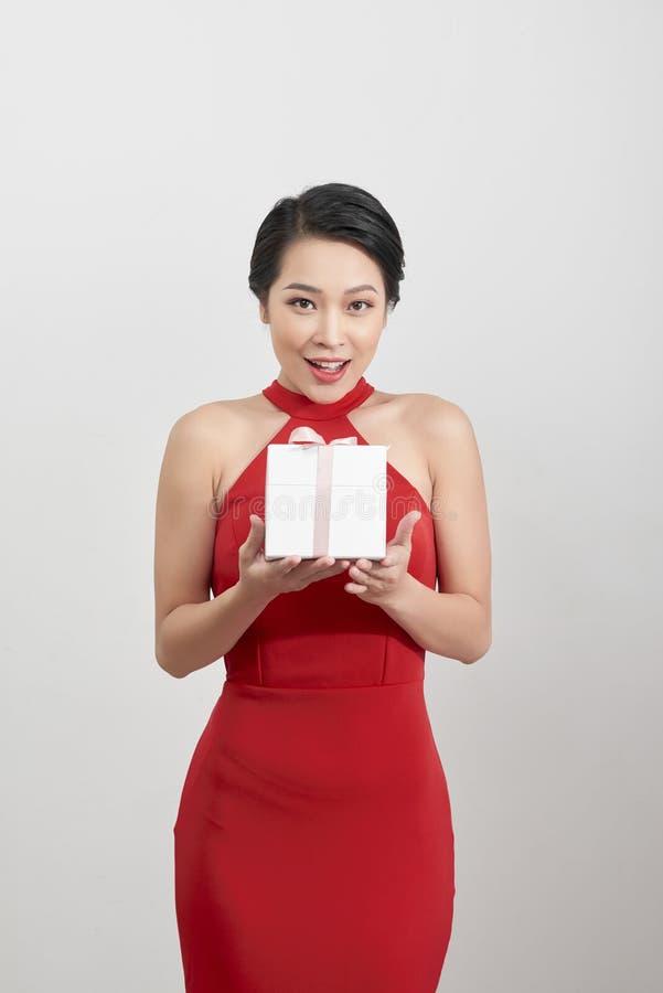 Bild av den älskvärda kvinnan i röd klänning med gåva royaltyfri fotografi