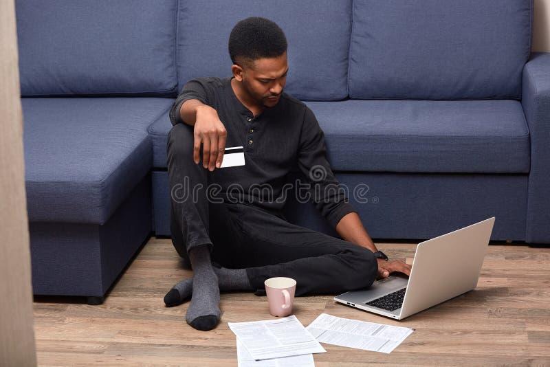 Bild av den allvarliga eftertänksamma Afroamerican mannen som hemma blir, förväxlas med online-tjänst, innehavkreditkort som ser arkivbilder