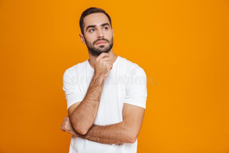 Bild av den allvarliga man30-tal i t-skjortan som trycker på hans haka, medan stå som isoleras över gul bakgrund royaltyfri fotografi