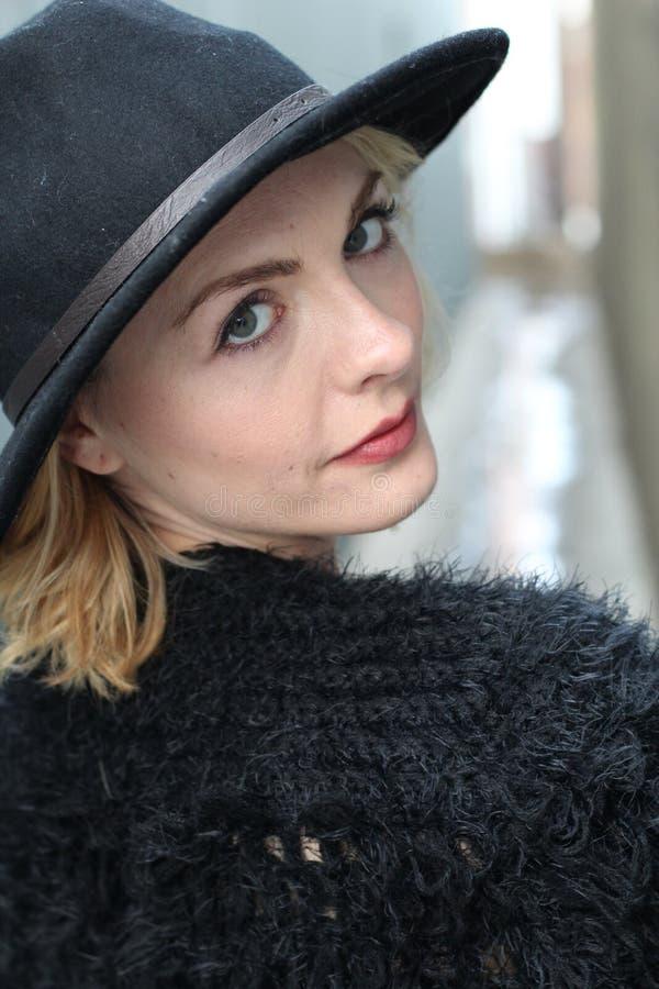 Bild av den attraktiva blonda kvinnlign som bär den svarta hatten, closeupstående av den stilfulla eleganta kvinnan, härlig flick royaltyfria bilder