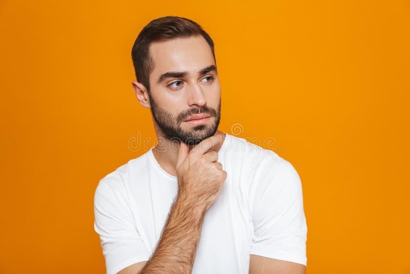 Bild av den attraktiva man30-tal i t-skjortan som trycker på hans haka, medan stå som isoleras över gul bakgrund arkivbild