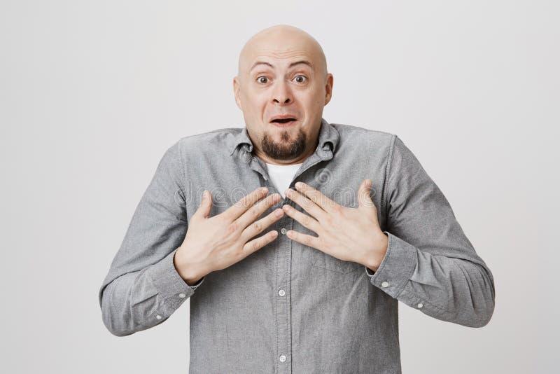Bild av den attraktiva mannen med det roliga, chockade och förvånade uttryckt som rymmer hans händer på bröstkorg över vit bakgru arkivbild