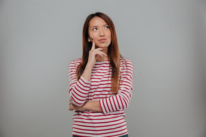 Bild av den eftertänksamma asiatiska kvinnan i tröjan som ser upp fotografering för bildbyråer