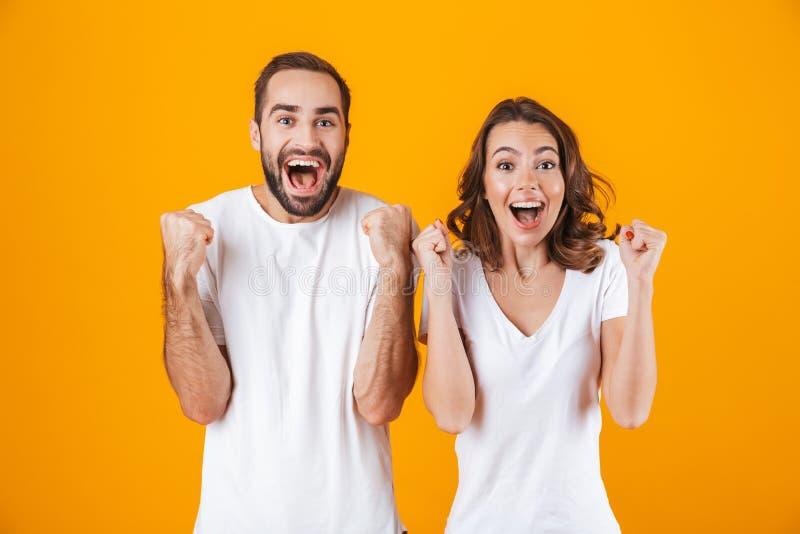Bild av den extatiska den folkmannen och kvinnan i grundläggande kläder som skrattar, medan stå tillsammans isolerat över gul bak royaltyfri foto