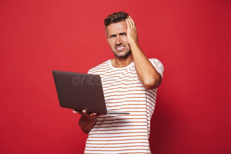 Bild av den förvirrade unga mannen i randigt t-skjorta le och holdi arkivbilder
