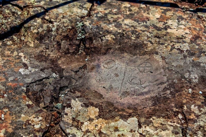 Bild av den forntida jakten på väggen av grottaockran Historisk konst axeln arkivbilder
